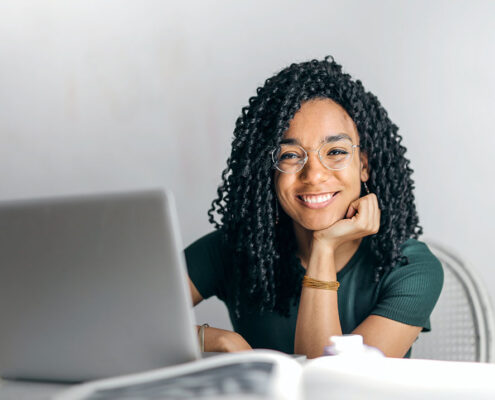 smiling woman, small business cpa, doing taxes at laptop