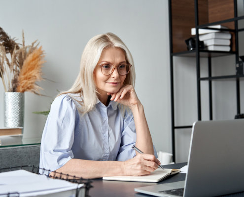mature woman talking with financial coach on laptop